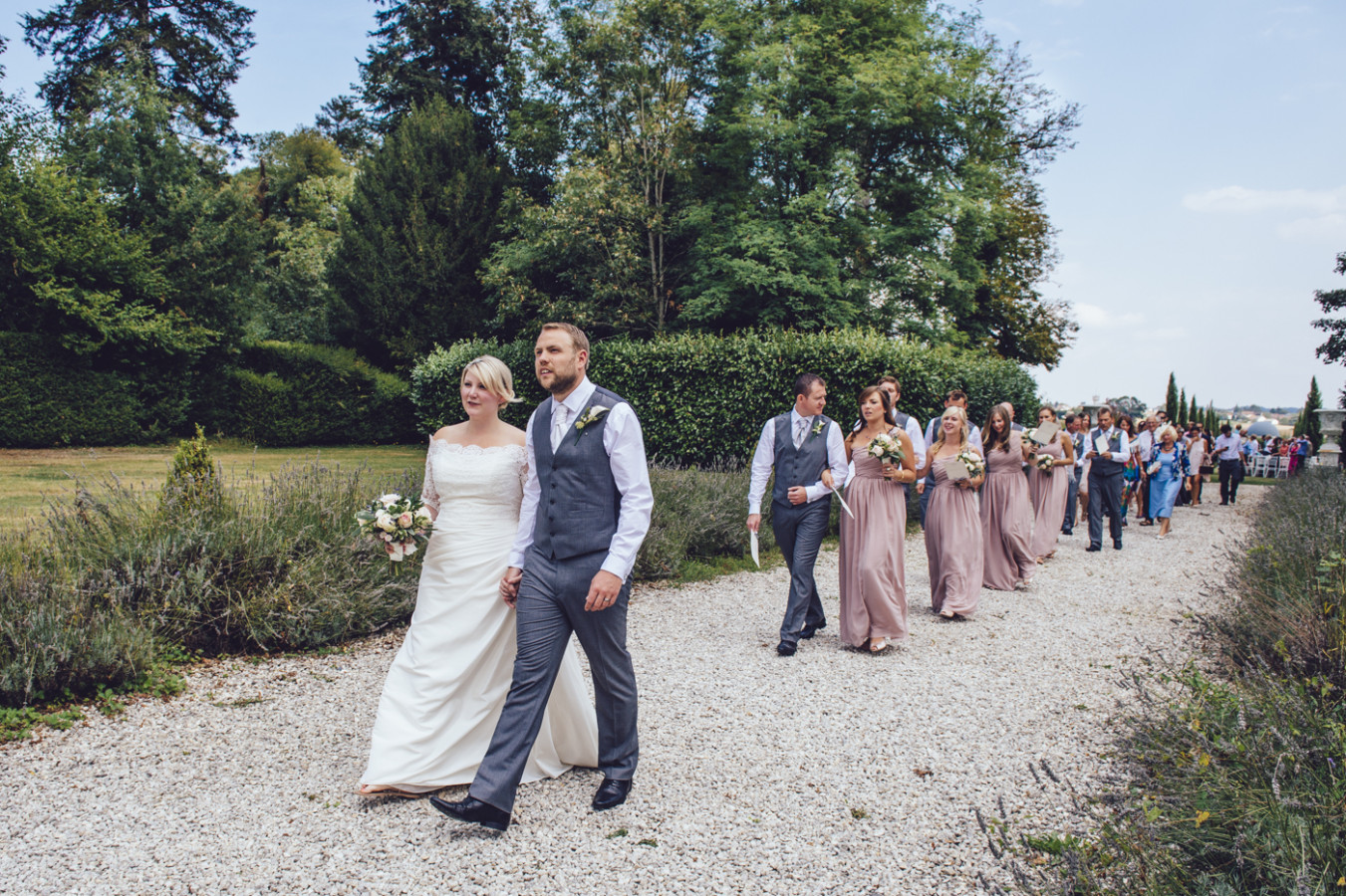 wedding photography in dordogne, france, bride, groom and wedding party walk in unison